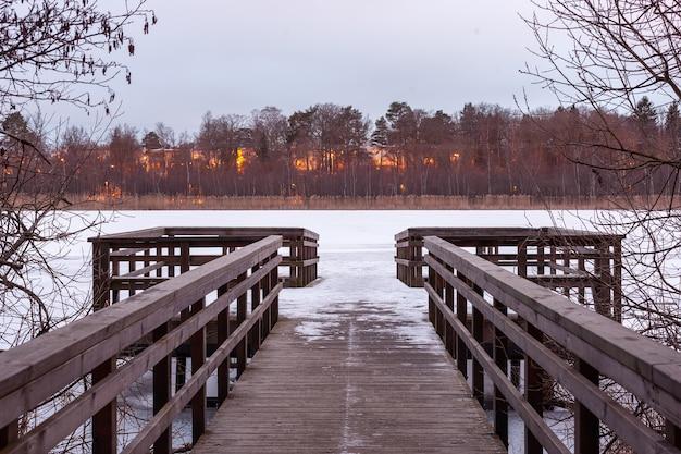 Bela foto de um caminho de madeira na margem do rio e uma floresta em chamas na costa oposta