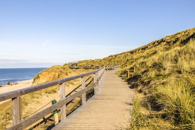 Bela foto de um caminho de madeira nas colinas na costa do oceano na ilha de sylt na alemanha
