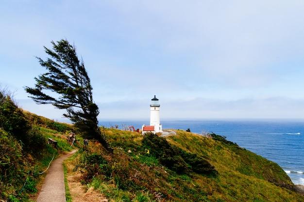 Bela foto de um caminho estreito em direção ao farol branco perto da falésia e do mar