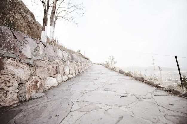 Bela foto de um caminho vazio ao lado de uma montanha com um céu nublado