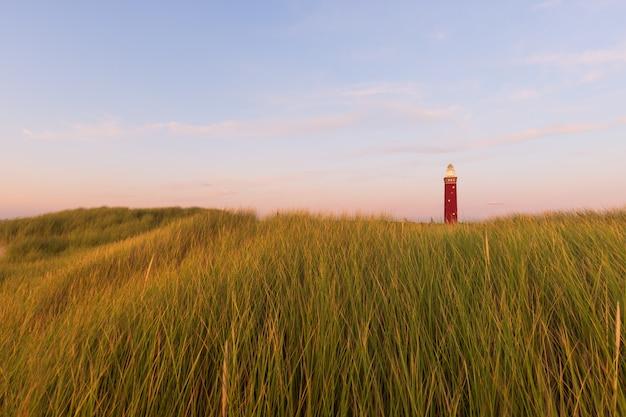 Bela foto de um campo gramado com um farol vermelho na distância e céu azul