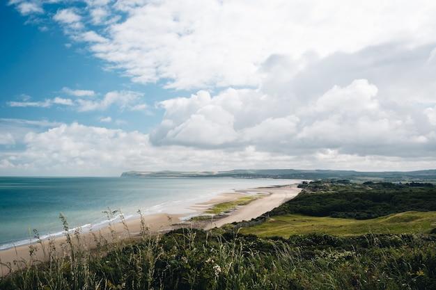 Bela foto de um campo gramado perto da costa da praia sob um céu nublado na frança