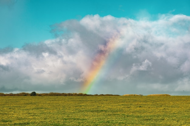 Bela foto de um campo gramado vazio com um arco-íris à distância sob um céu azul nublado
