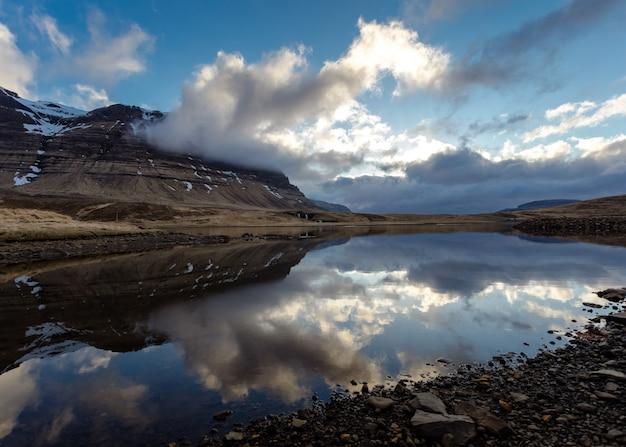 Bela foto de um campo rochoso com um lago e um céu de tirar o fôlego