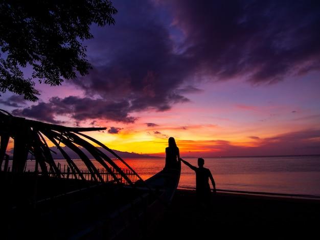 Bela foto de um casal na praia ao pôr do sol