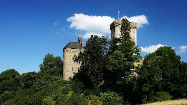 Bela foto de um castelo histórico, rodeado por árvores verdes sob o céu nublado