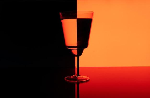 Bela foto de um copo com uma bebida em um fundo preto e vermelho com reflexos
