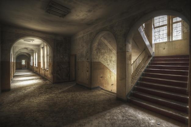 Bela foto de um corredor com escadas e janelas em um prédio antigo