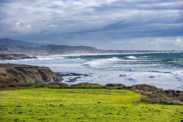 Bela foto de um farol em uma formação rochosa verde na costa do oceano