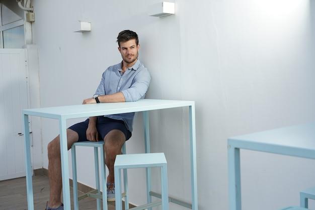 Bela foto de um homem atlético posando em um quarto mobiliado de branco