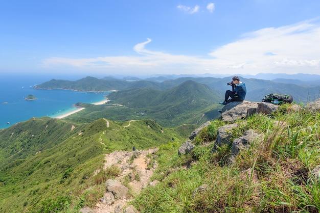 Bela foto de um homem capturando uma paisagem de colinas arborizadas e um oceano azul