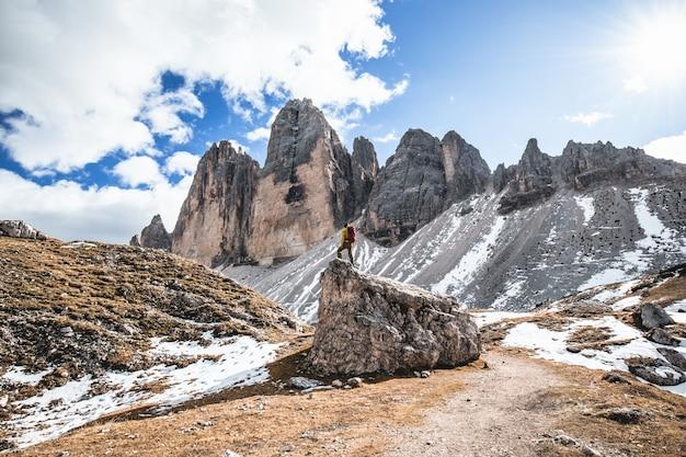 Bela foto de um homem de pé em uma rocha com colinas