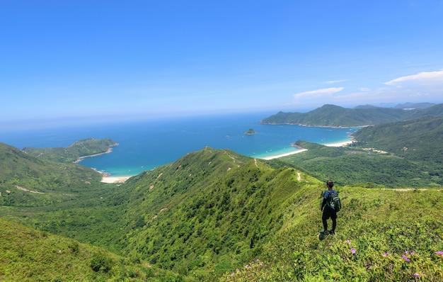 Bela foto de um homem em uma paisagem de colinas arborizadas e um oceano azul