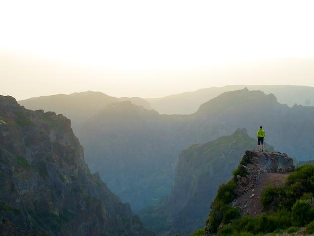 Bela foto de um homem parado na beira de um penhasco com vista para as montanhas sombreadas abaixo