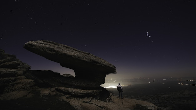 Bela foto de um homem parado nas colinas sob o céu noturno