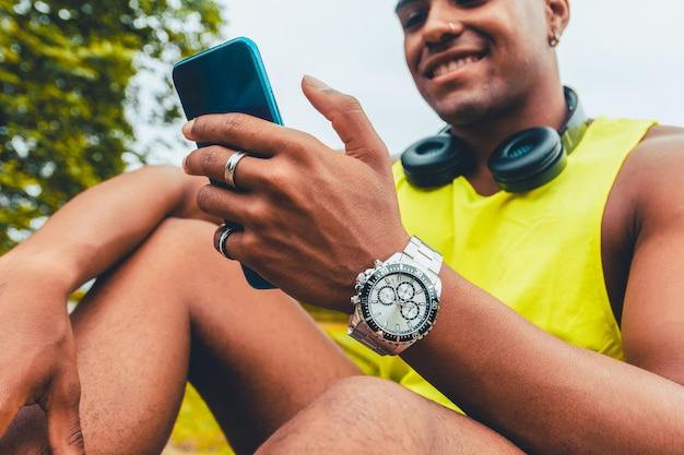 Bela foto de um jovem com fones de ouvido, sorrindo para o telefone enquanto está sentado em um parque