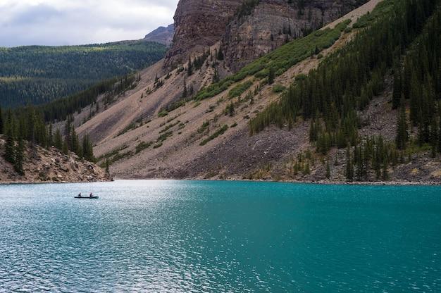 Bela foto de um lago azul perto das montanhas em um dia sombrio