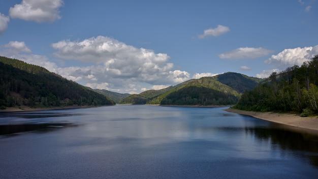 Bela foto de um lago cercado por montanhas com o reflexo do céu na água