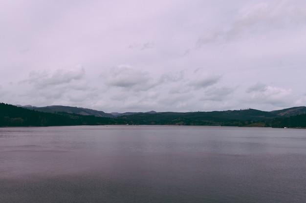 Bela foto de um lago com colinas no horizonte e céu nublado