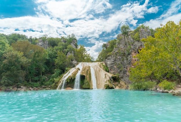 Bela foto de um lago com finas cachoeiras, rodeada por vegetação e montanhas