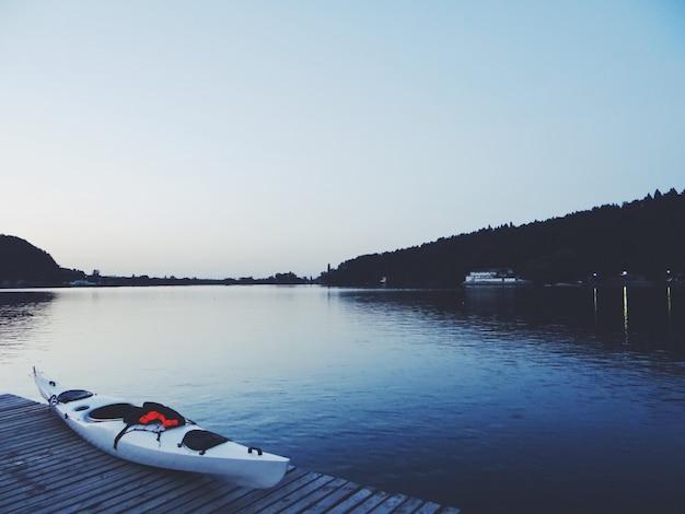 Bela foto de um lago com um caiaque branco em uma doca de madeira marrom