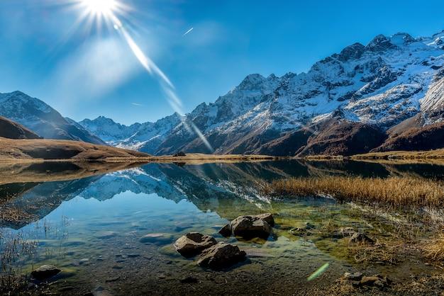 Bela foto de um lago cristalino ao lado de uma base de montanhas nevadas durante um dia ensolarado
