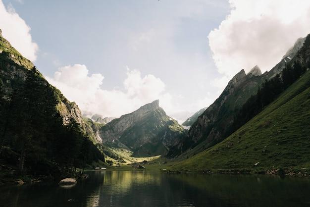 Bela foto de um lago rodeado por montanhas verdes