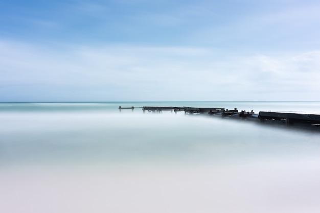 Bela foto de um mar calmo com uma ponte preta sob o céu azul
