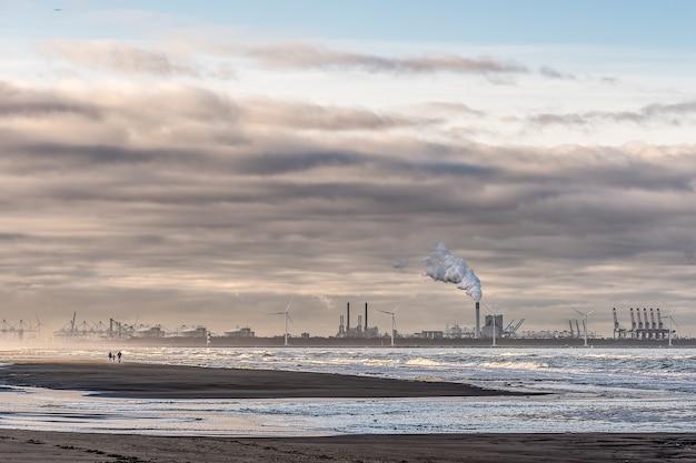 Bela foto de um mar com moinhos de vento e uma fábrica ao longe, sob um céu nublado
