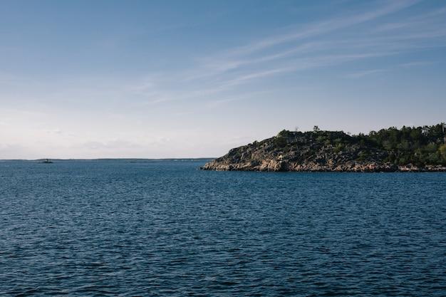 Bela foto de um mar com uma montanha à distância sob um céu claro
