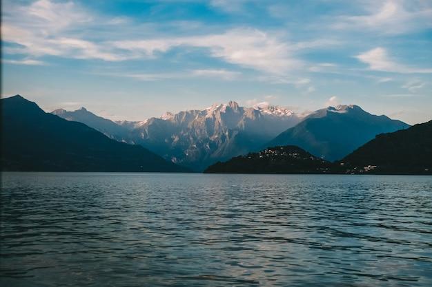 Bela foto de um mar e as montanhas rochosas à distância, com nuvens no céu