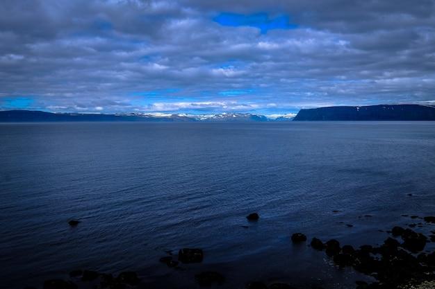 Bela foto de um mar e montanhas ao longe sob um céu nublado