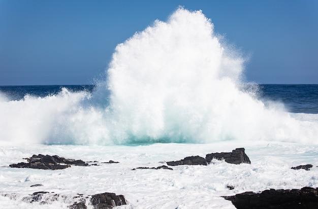 Bela foto de um mar ondulado contra rochas e penhascos