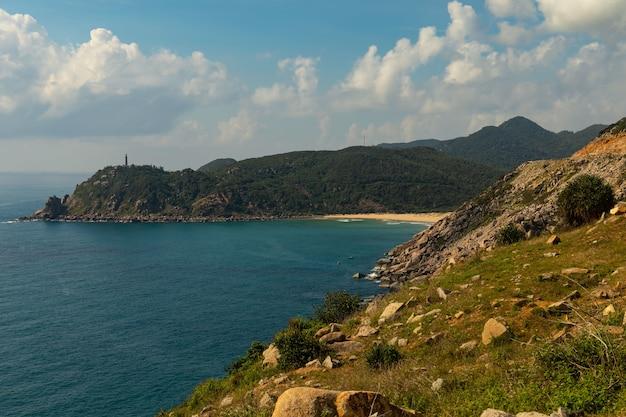 Bela foto de um mar perto das montanhas sob um céu azul