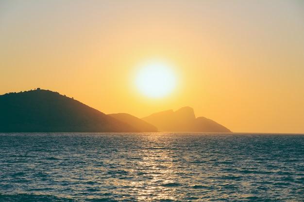 Bela foto de um mar refletindo a luz do sol com uma montanha à distância ao pôr do sol