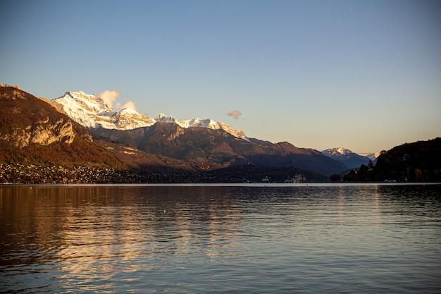 Bela foto de um mar rodeado por um cenário montanhoso sob o céu claro