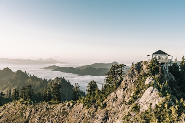 Bela foto de um mirante branco no topo da montanha perto de árvores com um céu claro no fundo