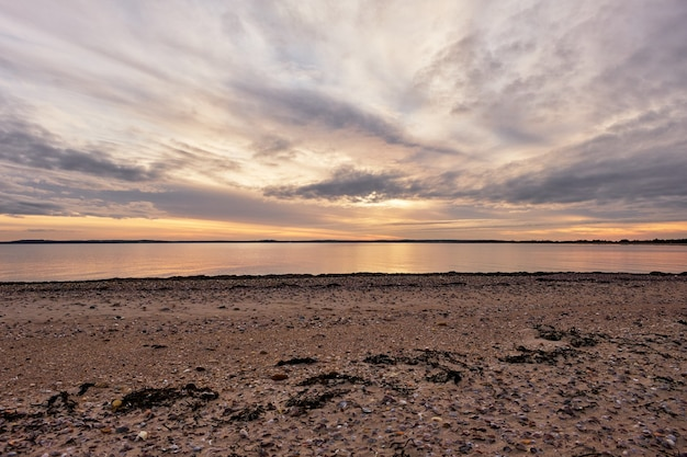 Bela foto de um oceano calmo com um cenário de pôr do sol em um céu azul nublado