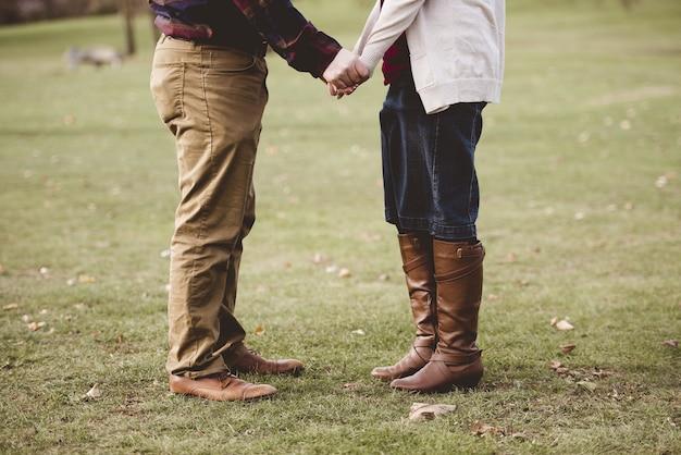 Bela foto de um par de mãos dadas em pé em um campo gramado com fundo desfocado