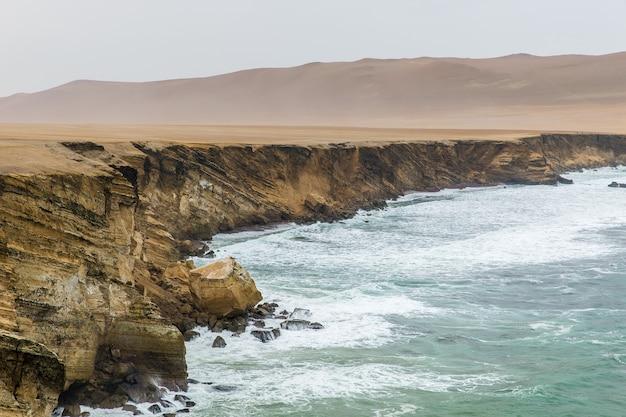 Bela foto de um penhasco perto do mar com montanhas ao longe