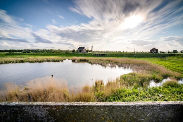 Bela foto de um pequeno lago cercado por vegetação sob um céu nublado