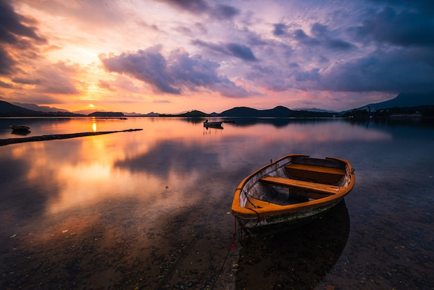 Bela foto de um pequeno lago com um barco a remo de madeira em foco e nuvens de tirar o fôlego no céu