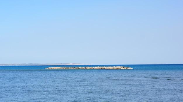 Bela foto de um pequeno terreno no meio de um oceano sob o céu azul