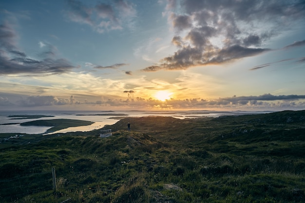 Bela foto de um pôr do sol na sky road, clifden, na irlanda, com campos verdes e oceano