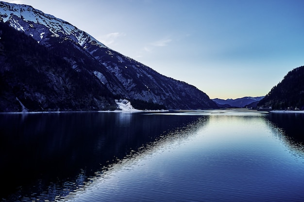 Bela foto de um rio com o reflexo das colinas nevadas e o céu