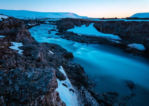 Bela foto de um rio em um campo rochoso