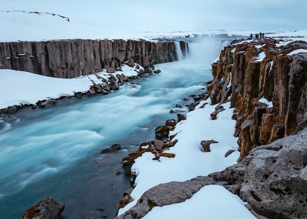 Bela foto de um rio em uma superfície rochosa de neve