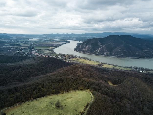 Bela foto de um rio entre colinas sob um céu nublado