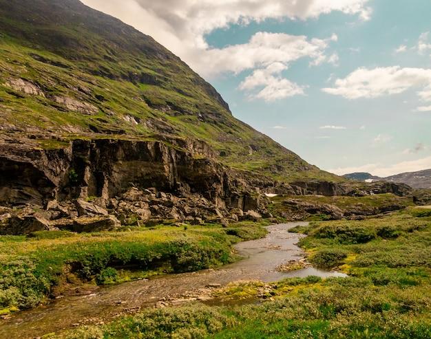 Bela foto de um rio que flui perto de altas montanhas rochosas na noruega