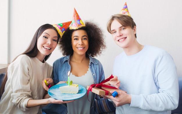Bela foto de uma aniversariante e seus amigos. menina asiática tem um pedaço de bolo. o cara tem um presente nas mãos. todos eles são felizes.